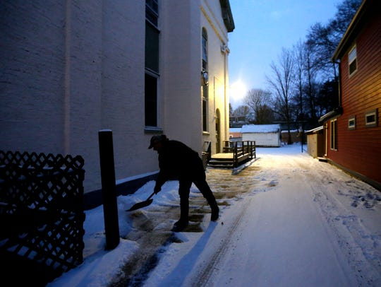 An AIMS Maintenance employee shovels the property of