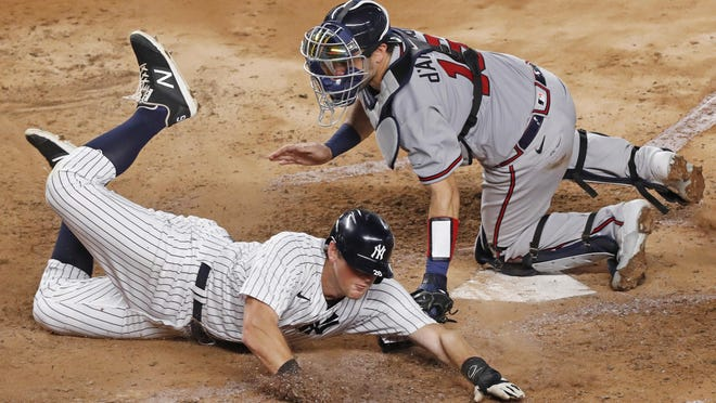 New York Yankees DJ LeMahieu scores on Aaron Hick's fourth-inning double as Atlanta catcher Travis d'Arnaud is late with the tag Wednesday in New York.