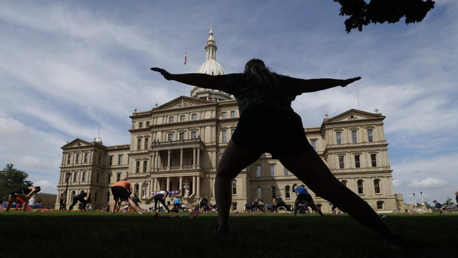 Tessa Baker exercises on the lawn of the state capitol in Lansing, Mich., Tuesday, July 21, 2020. The fitness workout and rally on the Michigan State Capitol lawn is intended to spotlight the benefits of exercise during the COVID-19 pandemic.