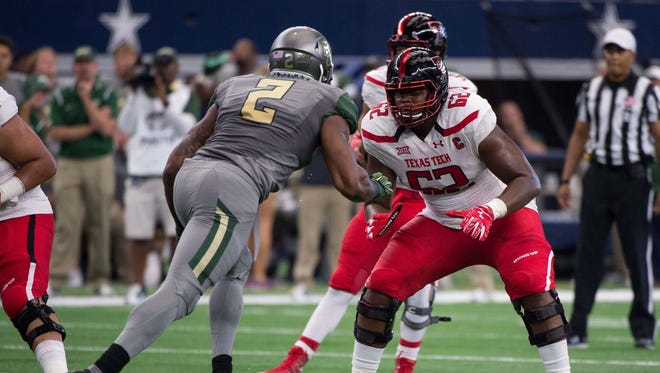 Texas Tech Red Raiders offensive lineman Le'Raven Clark (62) blocks Baylor Bears defensive end Shawn Oakman (2) during the game at AT&T Stadium. The Bears defeat the Red Raiders 63-35.