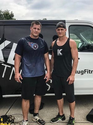 Karl Klug (left) of the Tennessee Titans stands with twin brother Kevin in front of the van for Kevin's personal training business.