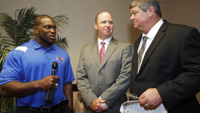 In this 2013 file photo, former Louisiana Tech defensive end IK Enemkpali, left, interviews Rice coach David Bailiff, right as Tech coach Skip Holtz looks on during the Conference USA football media day.