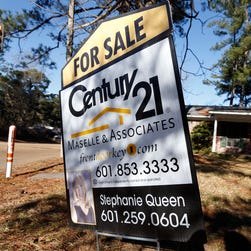 A realty sign is posted in front of a home for sale in Jackson, Miss.