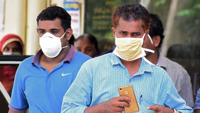 Indian residents wear face mask outside the Medical College hospital in Kozhikode on May 21. A deadly virus carried mainly by fruit bats has killed multiple people in southern India, sparking a statewide health alert.