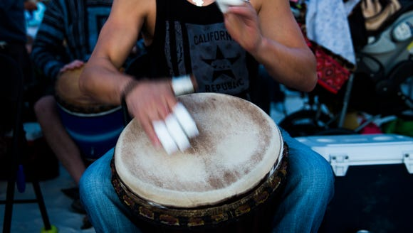 A drummer plays with taped fingers during the community