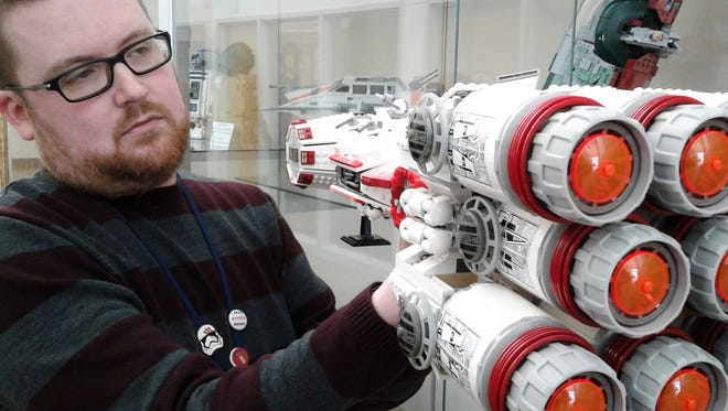 """Andrew Frisbie examines a huge, 1,748-piece Rebel Blockade Runner, just one the 242 """"Star Wars"""" Lego sets he has collected over the past two decades. About 20 are now on display at the North Liberty Community Library."""