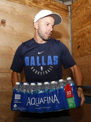 J.J. Barea, of Puerto Rico, loads water and other supplies for victims of Hurricane Maria.