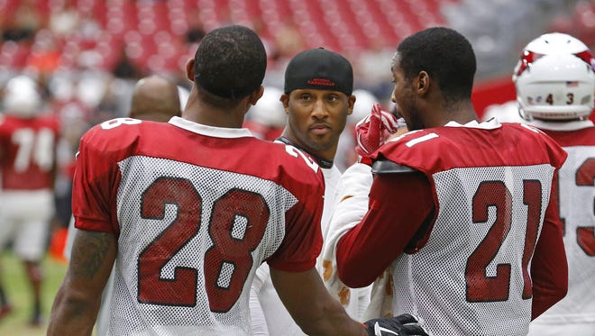 Arizona Cardinals cornerback Justin Bethel (28) and cornerback Patrick Peterson (21) talk with assistant Rod Hood during training camp Monday, August 17, 2015 in Glendale, Ariz.