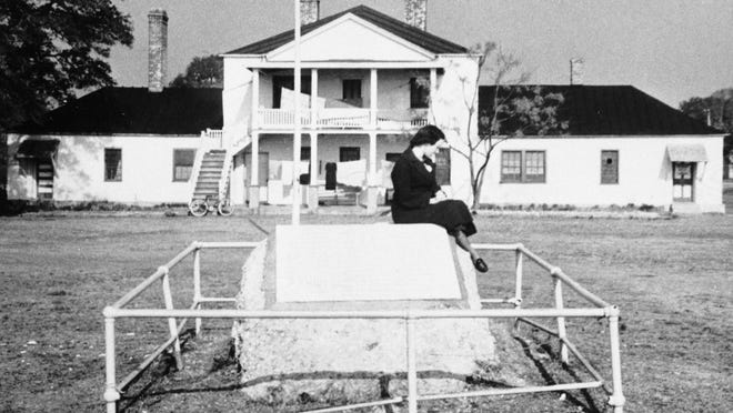 In this photo from 1955, a woman sits on the stone plaque to Fort Johnston and its 200-year role as a defender of the Cape Fear region.