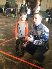 West York graduate Clayton Frey is vice president of Penn State's Bass Fishing Club. Here, he helps a boy with a fishing rod during the Great American Outdoor Show. The club helped with the Reel Kids casting contest run by the PA Bass Federation.