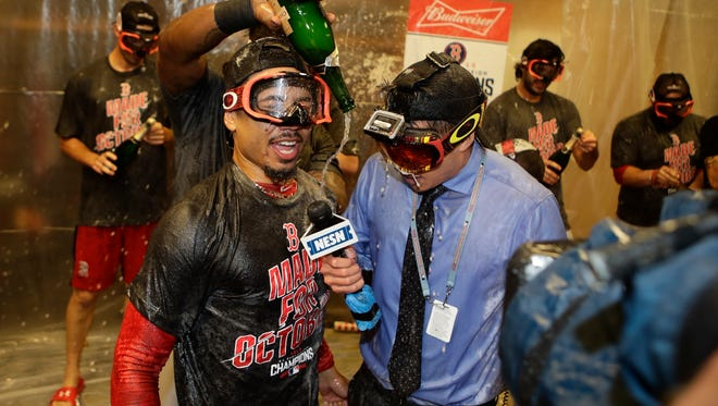 Boston's Mookie Betts responds to questions during an interview as his team celebrates clinching the AL East title on Sept. 28, 2016.