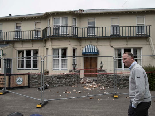 In this Thursday Nov. 24, 2016 photo, New Zealand Prime Minister John Key inspects damage to the Waiau Lodge Hotel in Waiau, New Zealand, after a magnitude 7.8 earthquake hit the region 10 days earlier. In terms of human life, the magnitude 7.8 earthquake that hit New Zealand this month was relatively merciful: just two fatalities. But geologically, it moved roads and mountains and even displaced the sea, leaving a formidable mark from which tourism, farming and life in general may need years to recover.