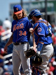 New York Mets catcher Kevin Plawecki (26) chats with Mets starting pitcher Noah Syndergaard (34) in the pitchers mound against the Washington Nationals during a spring training game at The Ballpark of the Palm Beaches.