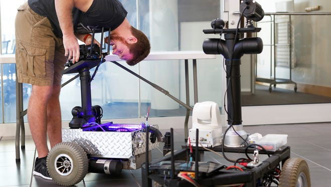 Zach MacAdams, a computer science major at Northern Kentucky University, realigns parts of  Duke, a robot, in the lobby of Griffin Hall. The robots are able to talk and move. NKU's spring class will design a robotic arm that will make it more useful for the Newport police and SWAT teams.