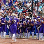 LSU players wait at home plate for junior catcher Kellsi Kloss (77) after Kloss hit a third-inning home run in the Tigers' 6-1 win over Auburn in the first round of the Women's College World Series in Oklahoma City Thursday.
