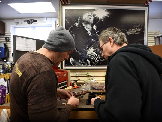 Matt Creter and Ron Yantz work to modify a guitar that was given as a Christmas present. A big poster of Stevie Ray Vaughan hangs in the background.