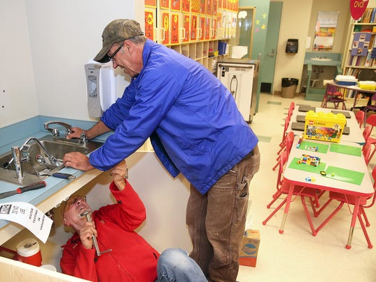 Bremerton School District plumber Rick Powell and general maintenance technician Pete Mullen change the faucets at Crownhill Elementary School in Bremerton. Water that came from certain faucets at the school had elevated lead levels, and the district responded by replacing the faucets or their components.