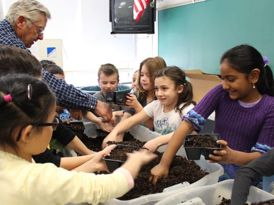 """Central School first-graders get dirty as they plant vegetable seeds on April 5 for the Wagner Farm Arboretum """"Growing to Give"""" educational program."""