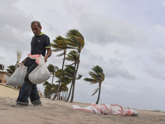 Jawad Muhammad collects sandbags from the beach to