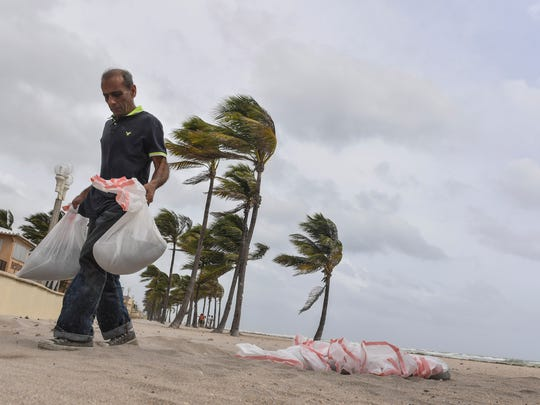 Jawad Muhammad collects sandbags from the beach to protect his home in Hollywood Beach, Florida.