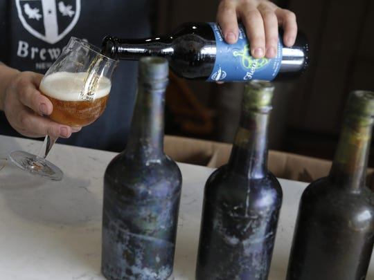 Jamie Adams pours a beer that was brewed using some yeast from beer bottles, right, recovered from the shipwreck of the SS Oregon at his St. James Brewery in Holbrook, N.Y.