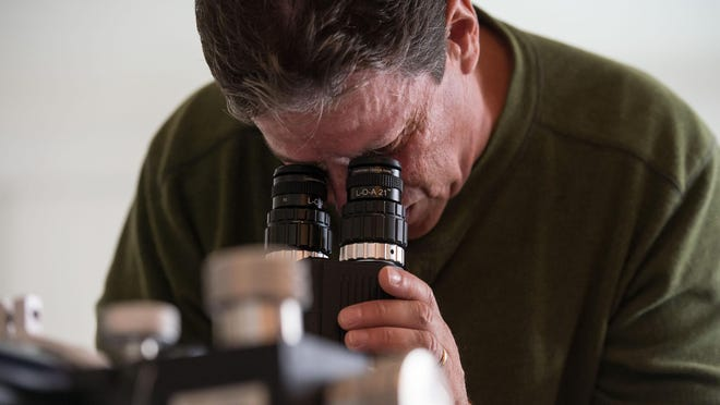 Russ Lederman makes adjustments to his custom telescope eyepieces during a demonstration at his office on Tuesday.
