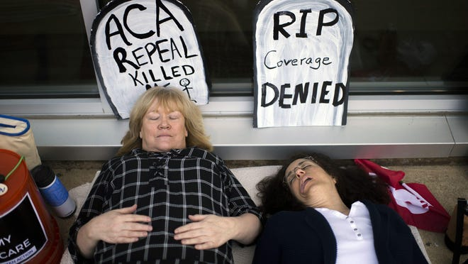 Maureen Quinn of Woodbury, left, and Maria Palmer of West Deptford play dead as protestors gather before a town hall meeting with Congressman Tom MacArthur (R-NJ) Wednesday, May 10, 2017 in Willingboro.
