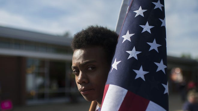 John Larrier of Maplewood stands with an American flag as protestors gather before the town hall meeting.