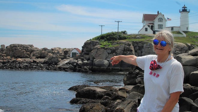 Elizabeth Kintzing, diving program officer for the UNH School of Marine Science and Ocean Engineering, points to the protected cove on the north side of Nubble Light, used by divers for easy entry and exit under most weather conditions.