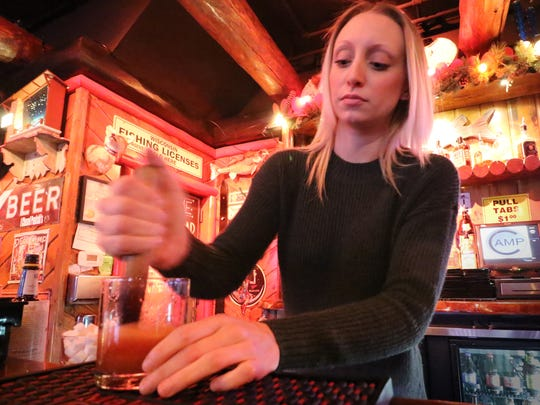 The Camp Bar's Amanda Handlos muddles bitters, sugar cubes, an orange slice and a cherry into a frothy mixture before adding ice, brandy and a splash of soda for the Camp Bar's version of the classic Korbel Brandy Old Fashion.