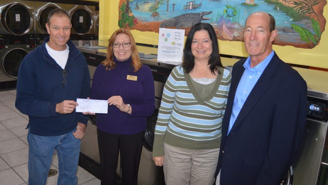 Sunshine Laundries co-owner Tom Rhodes presents a check to Melissa Winstead, Donna Lee Askan and Bob Calhoun, representing St. Lucie Habitat for Humanity.