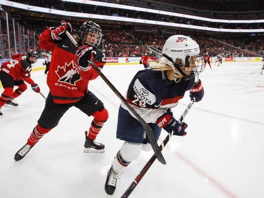 Team Canada's Meghan Agosta (2) hooks Team USA's Amanda Kessel (28) during first period National Women's Team series hockey action in Edmonton, Alberta, on Sunday Dec. 17, 2017. (Jason Franson/The Canadian Press via AP)
