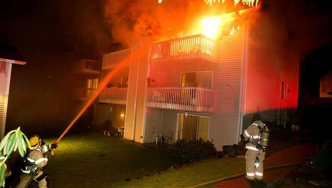Firefighters battle flames at Edgewood Villa apartments Tuesday night.