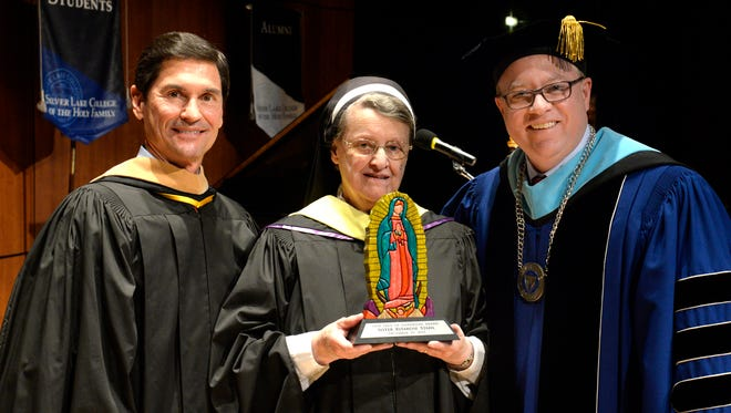 Sister Ritarose Stahl of the Franciscan Sisters of Christian Charity is presented with the Our Lady of Guadalupe Award by Silver Lake College board of trustees chair Eric Volcheff, left, and Silver Lake College president Chris Domes during the college's Winter Commencement Ceremony.