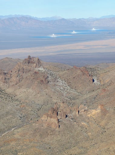 The Castle Peaks rise high above the desert floor.  At right is the Ivanpah Solar Power Facility in the distance.