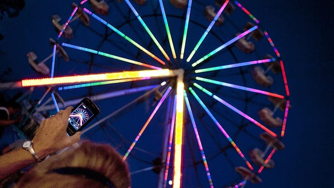Paula Simpson of Galesburg takes a cellphone video of the Ferris wheel on the midway of the Knox County Fair.