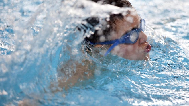 A young swimmer comes up for air as he swims a lap during water safety classes at the Hawthorne Center in this file photo.
