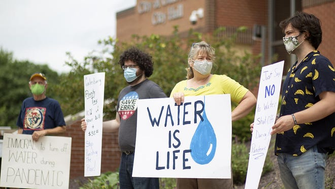 A group of citizens holds signs in front of Galesburg City Hall, 55 W. Tompkins St., on Friday, July 31, 2020. The group was demonstrating against the city's recent resumption of water line shut-offs for delinquent customers.