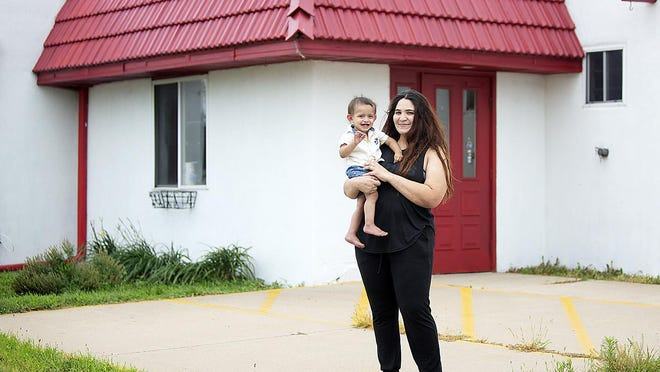 Owner Monserrat Chaidez holds Benjamin Chaidez near the main entrance of the soon-to-open Cielito's Cafe, 1488 N. Henderson St., on Monday afternoon.