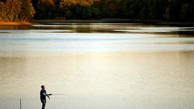 In this file photo, Casey Jacoby of Greenfield tries his hand at fishing as the sun sets on Lake Storey.