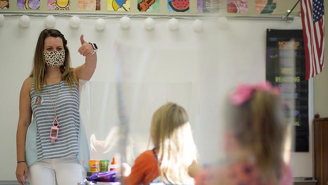 FILE: ROWVA second grade teacher Katie Sexton gives the thumbs-up sign to her students as in-school classes got underway in District 208 on Monday, Aug. 24, 2020. .