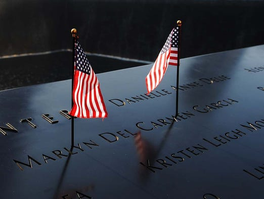 American flags decorate a name on the 9/11 Memorial during a ceremony marking the 12th anniversary of the Sept. 11, 2001, terrorist attacks at the World Trade Center site in New York City. Ceremonies honored the nearly 3,000 people killed when hijacked airliners slammed into the World Trade Center, the Pentagon and a field in Shanksville, Pa.