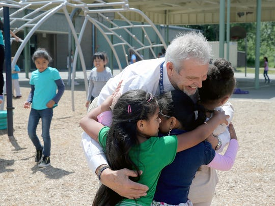 Armin Jahr Elementary School principal Mike Sellers hugs students during one of the final recesses of his tenure in education.