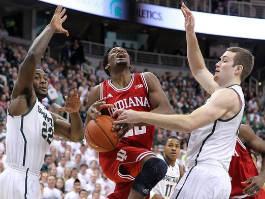 Jan 21, 2014; East Lansing, MI, USA;  Indiana Hoosiers guard Stanford Robinson (22) drives to the basket against Michigan State Spartans forward Matt Costello (10) and Branden Dawson (22) during the 1st half of a game at Jack Breslin Student Events Center. Mandatory Credit: Mike Carter-USA TODAY Sports