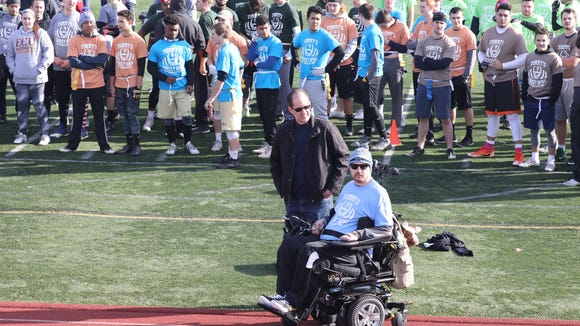 Tommy McGuire, is pictured with his dad Tommy during opening remarks on the sideline of the Clarkstown South High School football field in West Nyack, Nov. 25, 2017. The second annual Tommy McGuire Turkey Bowl was held as a fundraising event for the former student, paralyzed in a swimming pool accident.