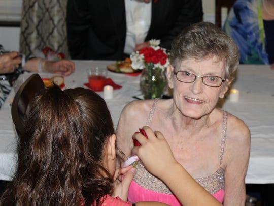 Heather Blackmon pins a rose onto resident Gail Garmon.