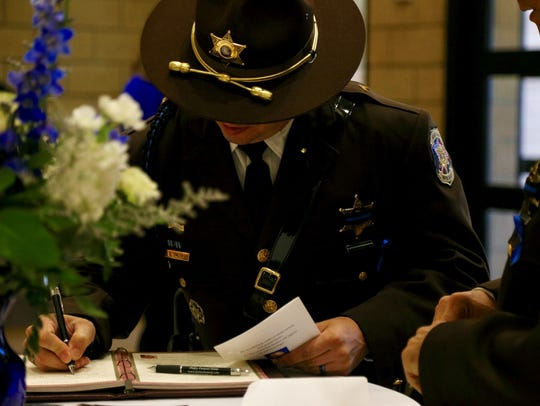Officers sign the guestbook at the funeral service for Oakland County Sheriff's Deputy Eric Overall on Tuesday, Nov. 28, 2017, at Mt. Zion Church in Independence Twp.