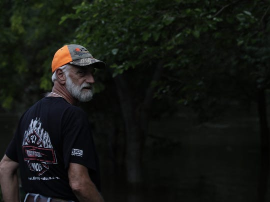 Former Rock Valley fire chief John Wallenburg monitors flood conditions in his backyard Friday. More than 50 homes were evacuated in Rock Valley, Iowa, after flooding hit the area Thursday. Residents were allowed to return to their home late Friday morning.