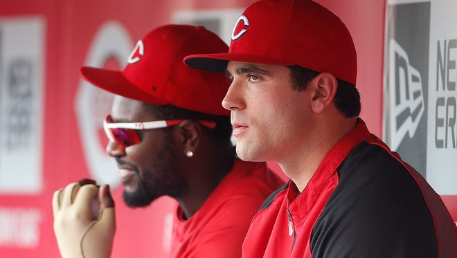 Reds first baseman Joey Votto, right, and second baseman Brandon Phillips chat in the dugout during a game against the Diamondbacks in July.