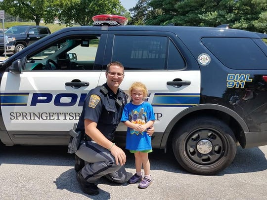 4-year-old Evelyn Pittman poses with Officer Cory Landis in front of his police vehicle Saturday afternoon at Springettsbury Township Park.